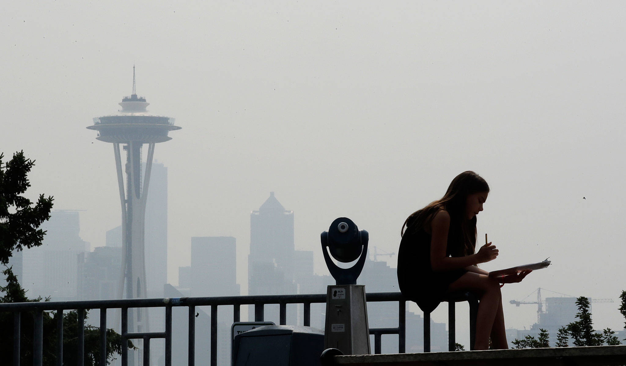 A woman works on a drawing next to an unused viewing scope as a smoky haze obscures the Space Needle and downtown Seattle last August as smoke from wildfires moved across the region. (Photo courtesy of The Herald/Elaine Thompson/Associated Press)